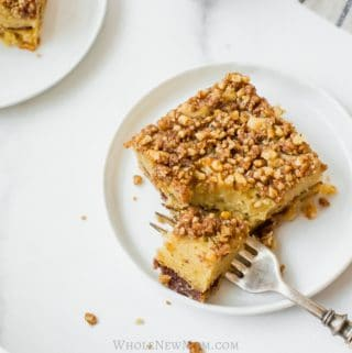 keto coffee cake on a white plate with a fork with a bite taken out of it - with the cake and a dish towel in the background