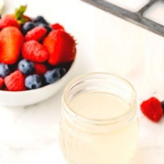 homemade keto simple syrup in a small mason jar on a white table with a bowl of berries in the background