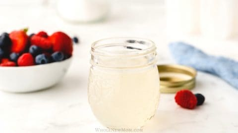 homemade sugar-free simple syrup in a small mason jar on a white table with a bowl of berries in the background