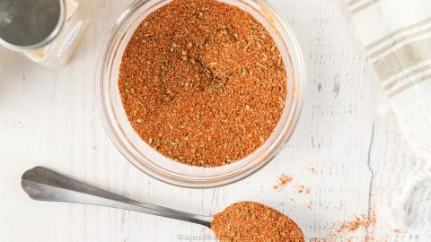 homemade chili powder in a glass jar with a spoon on the side on white table top