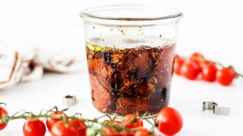 homemade sun-dried tomatoes in oil in glass jar on white table with cherry tomatoes in background