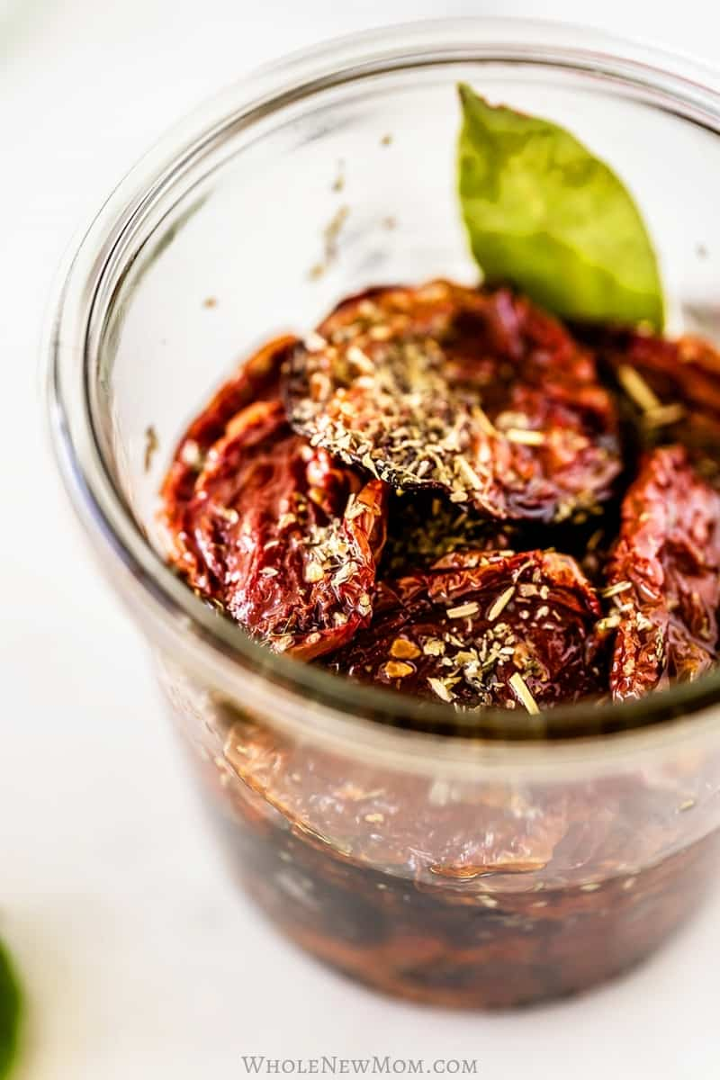 homemade sun-dried tomatoes in oil in glass jar on white table