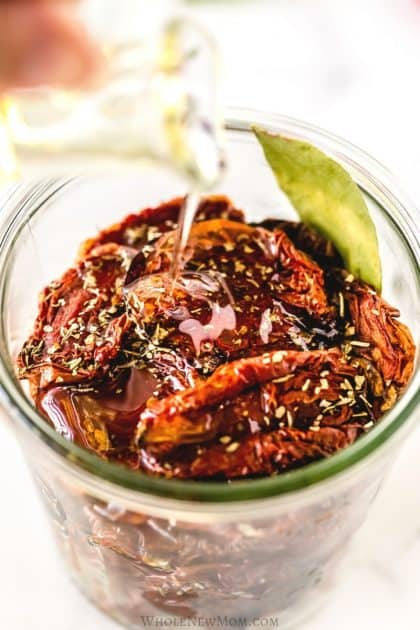 pouring oil on homemade sun-dried tomatoes in a glass jar