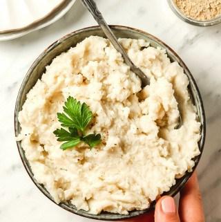 hand holding gray bowl of keto mashed potatoes
