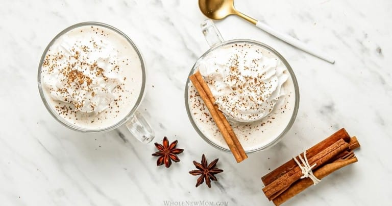 vegan eggnog in glass mugs with spoons, cinnamon sticks, and anise