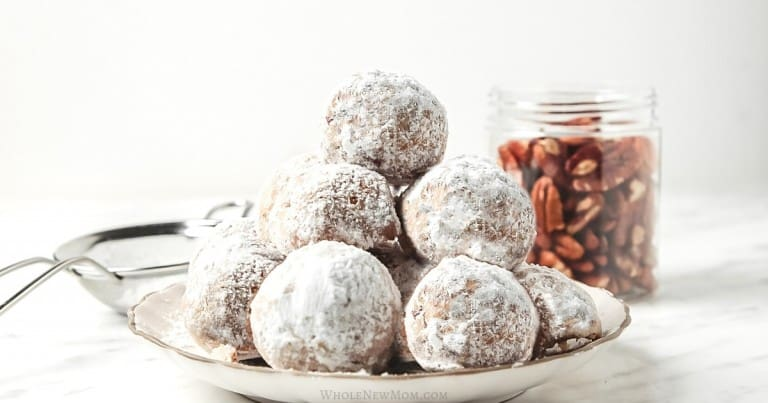 snowball cookies on white plate with pecans in the background