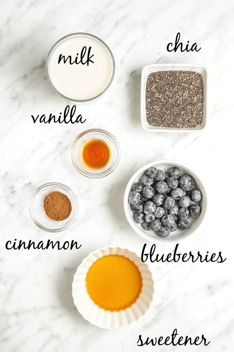 blueberry chia pudding ingredients in small bowls on marble tabletop