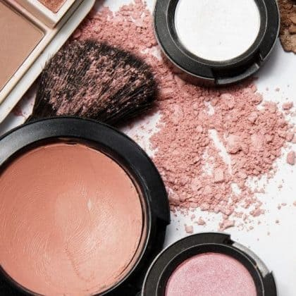 a make up brush with some pink powder blush in it and three compact blushes around it