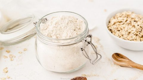 homemade oat flour in a jar with a wooden spoon