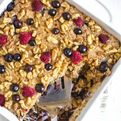 baked oatmeal cake topped with nuts and dried fruits in a white plate