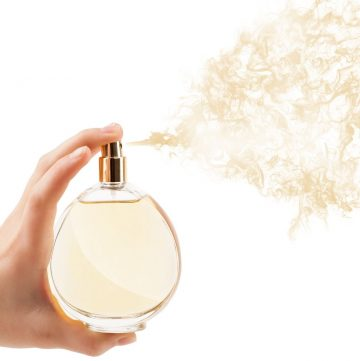 hand spraying a bottle of perfume