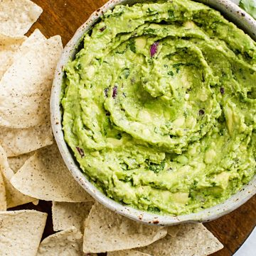 guacamole in a bowl with some tortilla chips surrounding it