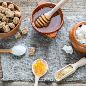 honey and different types of sugar in bowls, scoop, and wooden spoons
