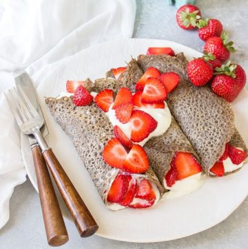 buckwheat pancakes with strawberries and cream on a plate