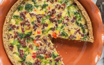 one whole veggie quiche with a missing slice