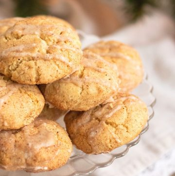 pile of eggnog cookies on a clear glass plate