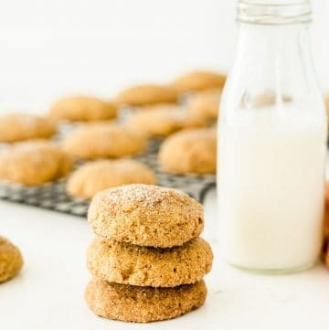 three pumpkin snickerdoodles on top of one another with milk on the side