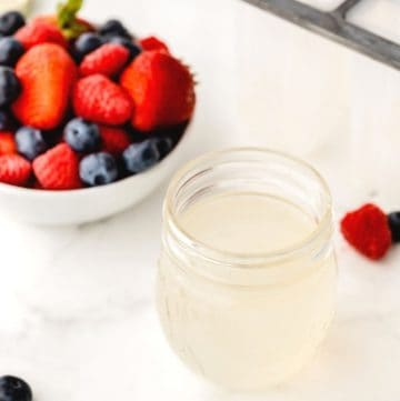 sugar-free syrup in a glass container and a bowl of berries in the background
