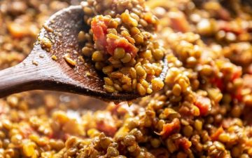 lentil curry and wooden spoon with a scoop of it