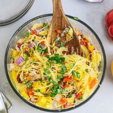 squash salad in a bowl with wooden spoon
