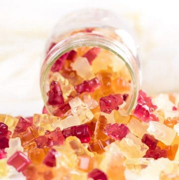 colorful homemade gummies coming out of a glass jar
