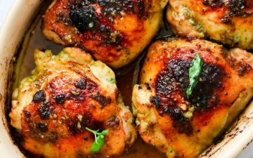 chicken thighs in a baking dish garnished with basil