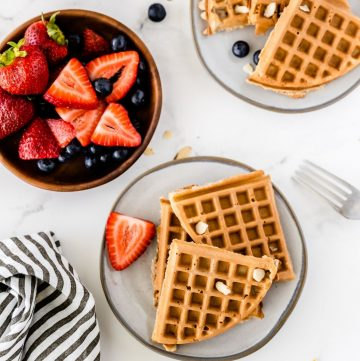 waffles on a plate and a bowl of strawberries and blueberries