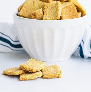 cheez its in a bowl and some pieces on a white tabletop