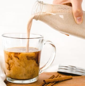 vegan pumpkin spice creamer being poured into glass mug