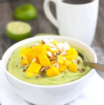 avocado lime pudding in a bowl topped with mango