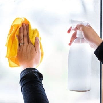 window cleaner in spray bottle pointed at the window