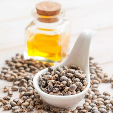 spoonful of castor beans and a bottle of castor oil in the background