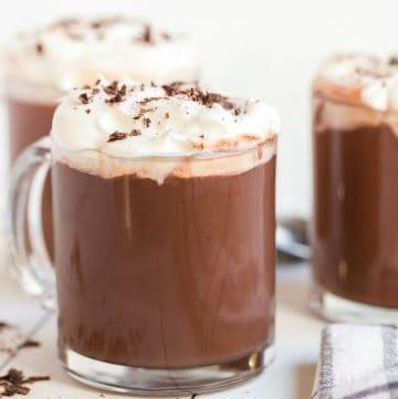 hot chocolate in mugs topped with whipped cream and chocolate shavings