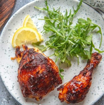 oven barbecued chicken with slice of lemon and garnish on a plate