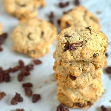 paleo cookies stacked together with raisins around it